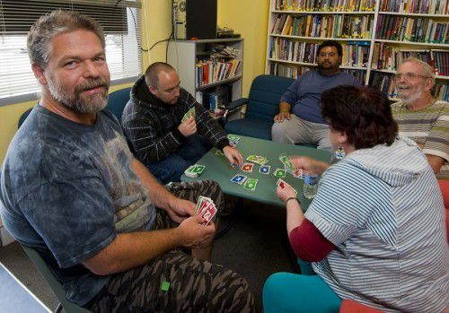 Missionheart leader Jason Hayduk, left, chats with clients Michael, Leon, Rogers and Marie over a game of cards in the Griffin Centre. Photo by Gary Schafer