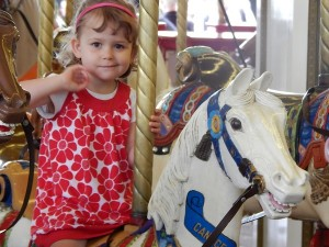 Tia Evangelista, 3, loves to ride the merry-go-round.