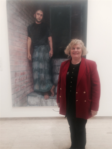 Helen Musa in front of the Archibald entry painting of her son Omar.