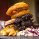 Pork Ribs - Sticky bourbon BBQ ribs served with a side of cajun spiced chunky chips & topped slaw with onion rings