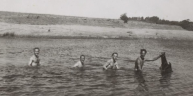 "Swimming in Canberra in 1945 oblivious of ""a large, amphibian dog-like creature""."