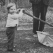 Two-year-old Rewa helps her dad mow the backyard of the Queanbeyan Presbyterian Manse in 1935.