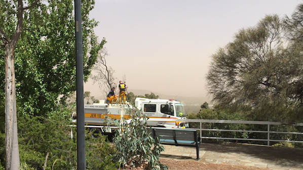 An Emergency Services crew keeps an eye on the dust storm across the Woden Valley from atop Red Hill.