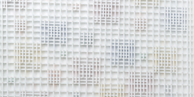 """Hilarie Mais' """"Cluster Ghost 2016""""... the work appears to glow, an effect due to primary colours painted on the back of the clusters of wooden strips reflecting off the wall behind the work."""