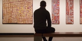 A visitors sits infront of works by Nancy Ross Nungurrayi and Naata Nungurrayi at the Drill Hall Gallery. Photo, Lannon Harley, ANU