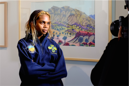 Aretha Namatjira in front of a painting by Kevin Namatjira. Photo by Greer Versteeg