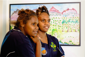 """Cheyanne Driffen and Semra White, from Ntaria School, in front of """"Tjurretja – West MacDonnell Ranges"""" by Ntaria School students. Photo by Greer Versteeg"""
