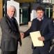 MLA Steve Doszpot receives the petition from Paul Haesler.