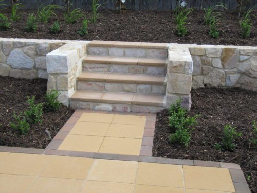 A stone retaining wall with Bink's paver treads.