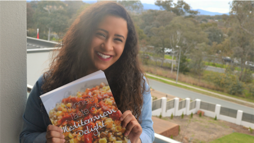 "Cookbook co-author Farah Khairat with a copy of ""Minnie's Taste of Mediterranean Delight""."