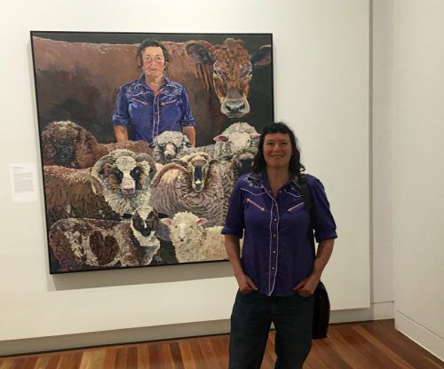 Lucy Culliton with sheep in foreground and 'Bison' at back.