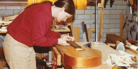 Gillian works on a mandolin.